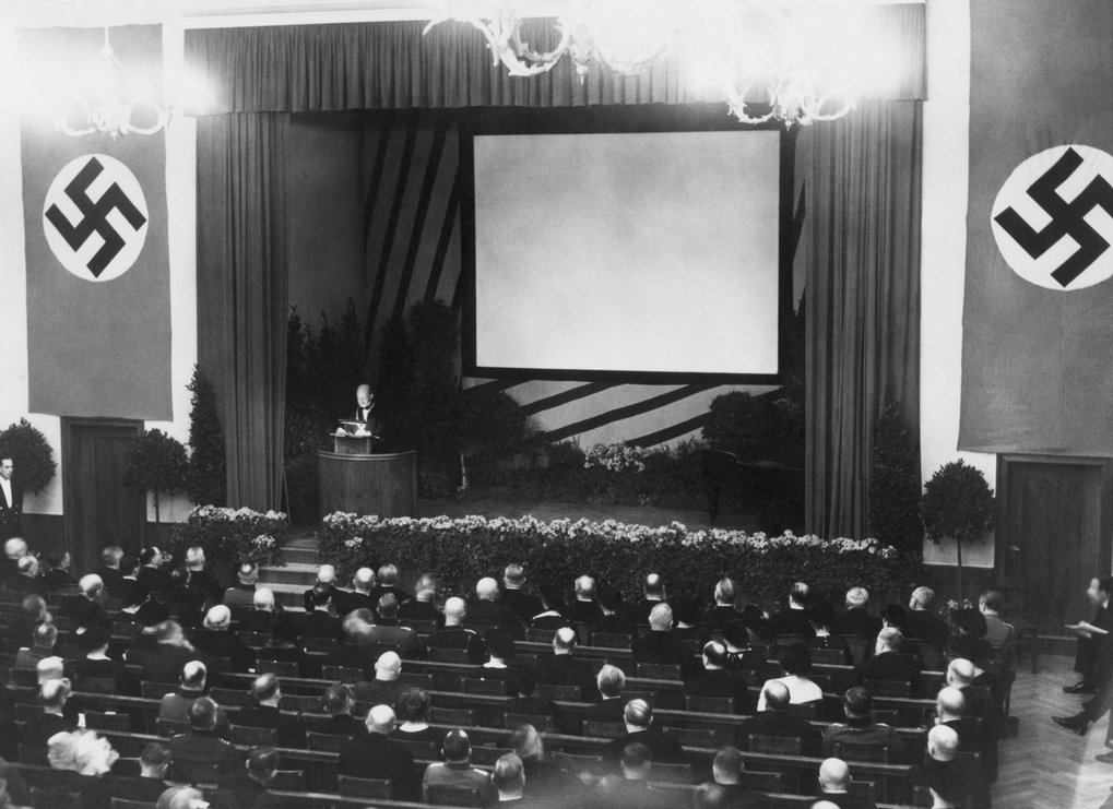 "<span lang=""en"">Max Planck at the lectern in the Goethe Auditorium at the 25th anniversary of the KWG, 1936.</span>"